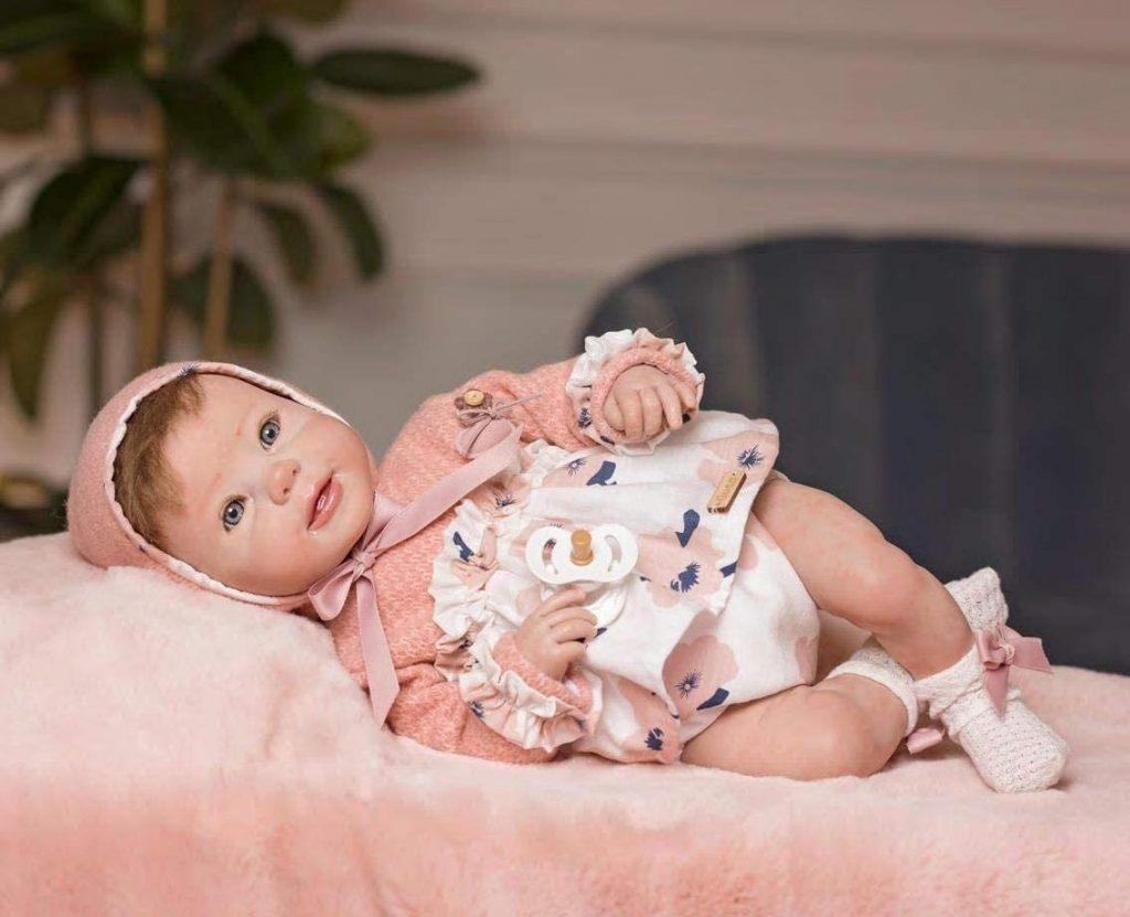 Diese realistische Guca-Puppe trägt ein kleines Kleid mit wunderschönen Blumen.