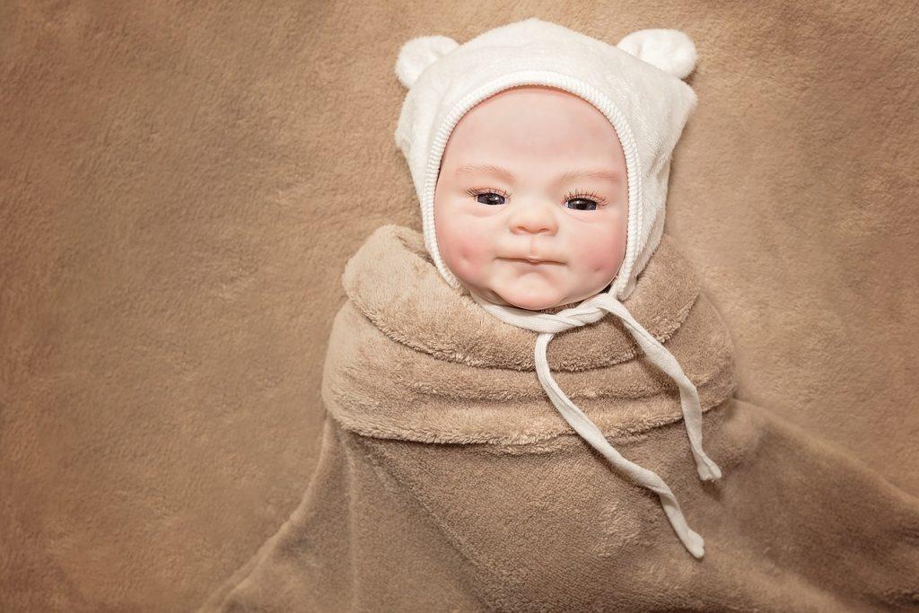 Dieses reborn Baby trägt einen Teddybärenhut.