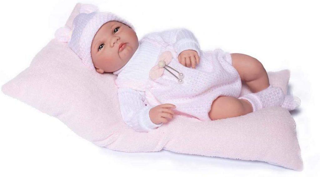 Das reborn Baby Elsa trägt weiße und rosa Kleidung.